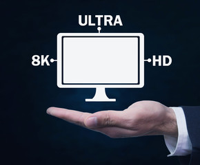 Hand holding computer monitor. 8K Ultra HD. Digital Video Technology