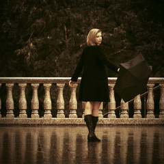 Young fashion woman in black coat with umbrella walking on city street