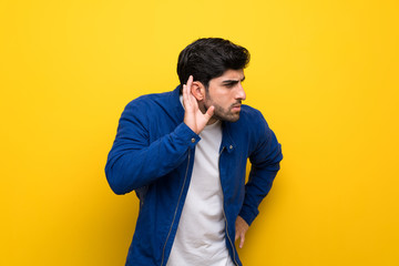 Man with blue jacket over yellow wall listening to something by putting hand on the ear