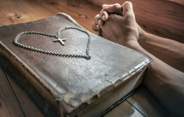 Young man praying with the cross necklace on holy bible. symbol of christian concept.
