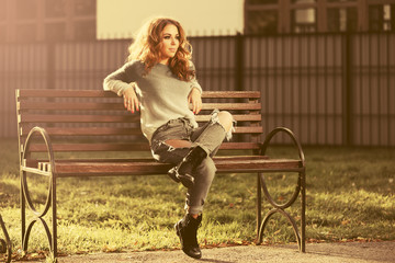 Happy young fashion woman in ripped jeans and gray pullover