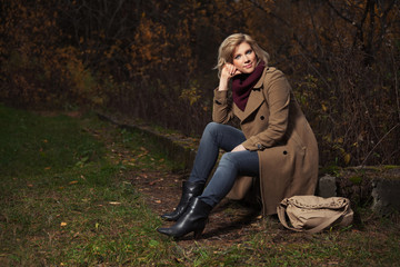 Happy young fashion woman with handbag in autumn park