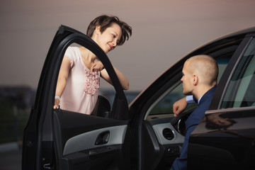 Happy young couple talking through the car door