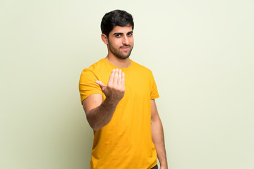 Young man over pink wall inviting to come with hand. Happy that you came