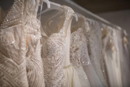 Wedding dresses hang on hangers. Factory of wedding dresses.