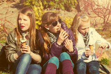Happy teen girls eating an ice cream outdoor