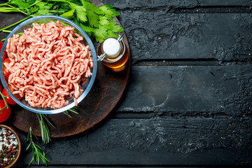 Raw minced meat in a bowl with spices and herbs.