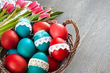 Obraz Kosz pełen kolorowych pisanek , w tle różowe tulipany - fototapety do salonu