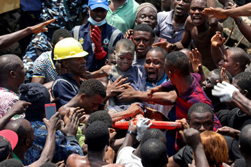 A Picture and its Story: Nigerian boy pulled from rubble remains calm amid chaos