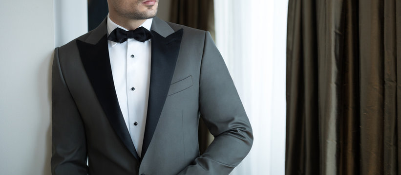 Man model in expensive custom tailored tuxedo, suit standing and posing indoors