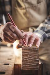 Handwerker markiert ein Stück Holz mit dem Bleistift