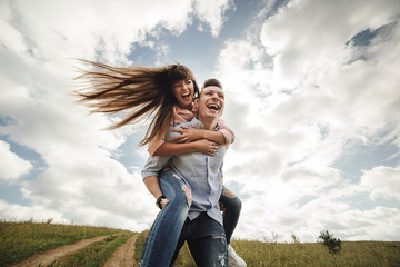 crazy young couple emotionally having fun, kissing and hugging outdoors. Love and tenderness, romance, family, emotions, fun. having fun together