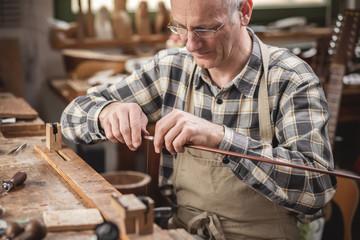 Instrumentenbauer bei der Drahtumwicklung eines Geigenbogens