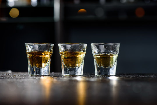 Three glasses of whiskey on a dark wooden bar in a nightclub. Close-up. Space