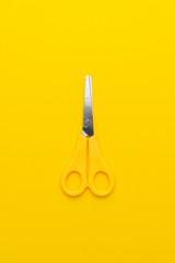 children's scissors on the yellow background. vertical orientation