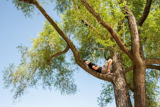 Man lying on tree branch