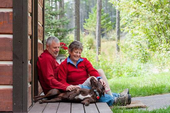 Smiling couple sitting with dog on porch