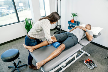 Physiotherapist giving leg massage to a man in clinic