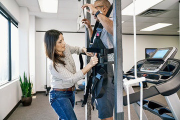 Physiotherapist helping patient to wear treadmill belt
