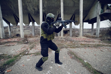 Armed special forces soldier terrorist in dark uniform and helmet aiming a rifle in front of ruined building