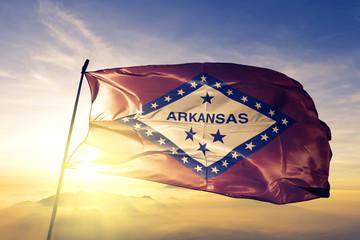 Arkansas state of United States flag waving on the top sunrise mist fog Fototapete