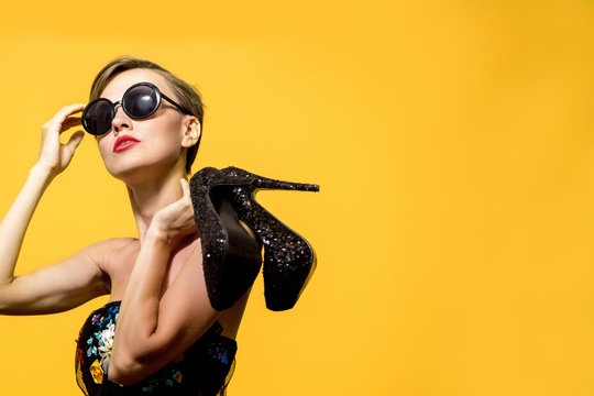 Fashionable woman wearing sunglasses holding high heels over yellow background