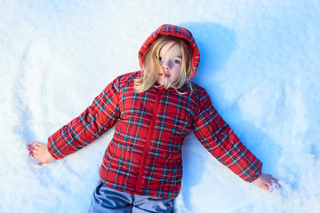Happy child girl playing on a winter walk in nature. Kid making snow angel. Top view