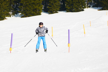 Child skiing in mountains. Active teenager kid with safety helmet and goggles. Ski race for young children. Winter sport for family. Kids ski lesson in alpine school. Young skier racing in snow