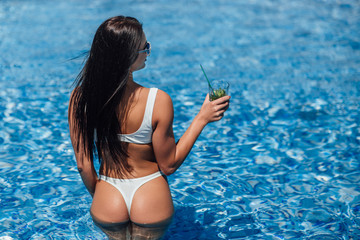 Young beautiful girl in a white swimsuit with a beautiful figure bathing in the pool and drinking a refreshing cocktail. .View from behind.