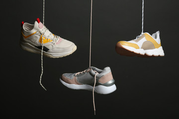 Wall Mural - Different sneakers hanging on black background. Stylish shoes