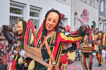 Colorful carnival figure with wooden ratchet. Street Carnival in Southern Germany - Black Forest.