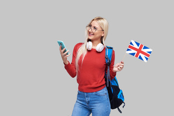 Online Education, foreign language translator, english, student - smiling blond woman in headphones holding mobile phone and British flag. Distance learning