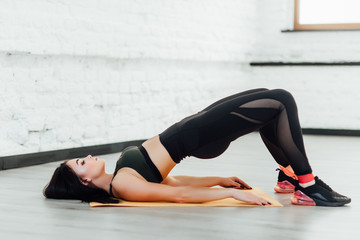 Brunette,athletic woman in squat together in gym.Fit girl  is exercising with resistance band for lower body relief. She is wearing sport clothes and sneakers