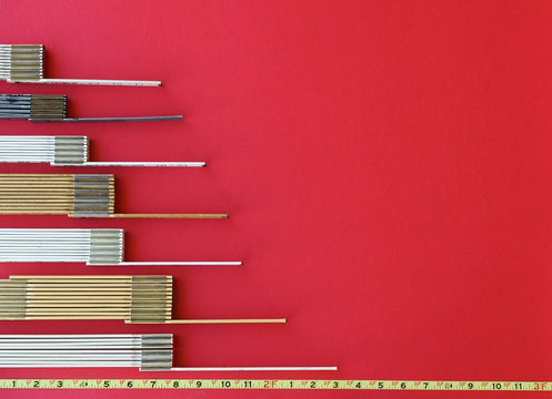 Folding rulers in metric and inches form a chart or graph in 3:2 format with baseline representing measurement, metrics, precision, increase, decrease, accuracy with copy space on red background.