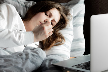 A young cute girl on a sunny day in a white jacket lies on the bed and looks at her nails. A laptop is standing nearby