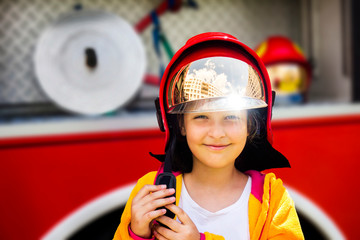 Cute young girl trying on real fireman's helmet standing in front of firetruck.