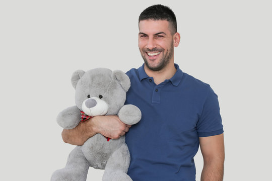 Portrait of a young handsome man holding a big teddy bear