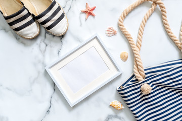 Travel composition on a marble background. Women's desk with striped sandals, beach bag, seashells and blank picture frame. Lifestyle of traveler, beauty blogger, digital nomad, hipster.
