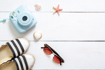 Summer holiday composition, traveler accessories on white wooden desk: sunglasses, sandals, instant camera, sea shell and star. Vacation, relaxing, sea beach resort, summer holidays concept