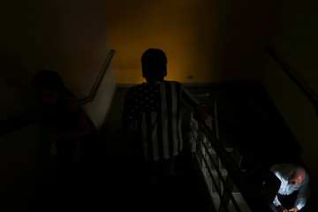 A person wearing a t-shirt with the design of a black and white U.S. flag climbs the stairs of a commercial center in Caracas