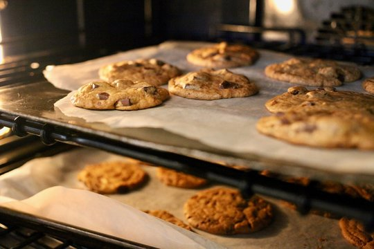 Fresh chocolate chip cookies being baked in an oven