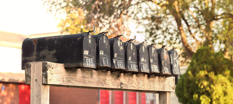 Old Rusted US Mailboxes on Wooden Post