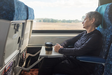 Three quarter length view of senior woman with grey hair in train seat with reusable coffee mug (selective focus)