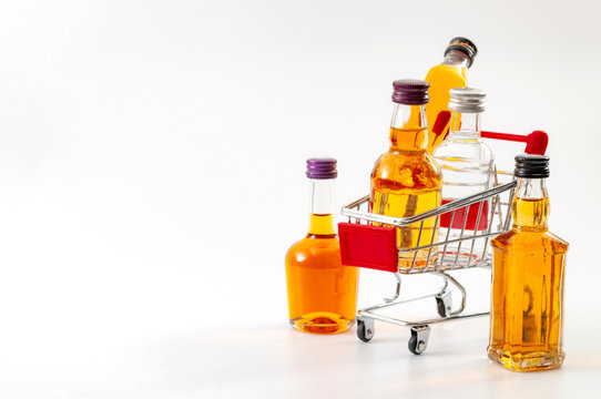 Buy booze, shopping the liqueur aisle and purchase of alcoholic beverages concept theme with mini bottles of alcohol in a small supermarket cart isolated on white background with copy space
