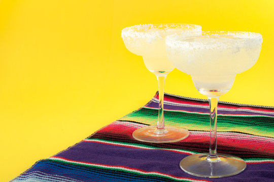 Happy Cinco de Mayo, Mexico fiesta and cocktail party concept theme with two margaritas and a Mexican stripped pattern rug named serape isolated on yellow background with copy space