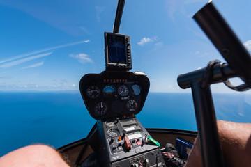 Cockpit eines Helikopters beim Flug über das Meer