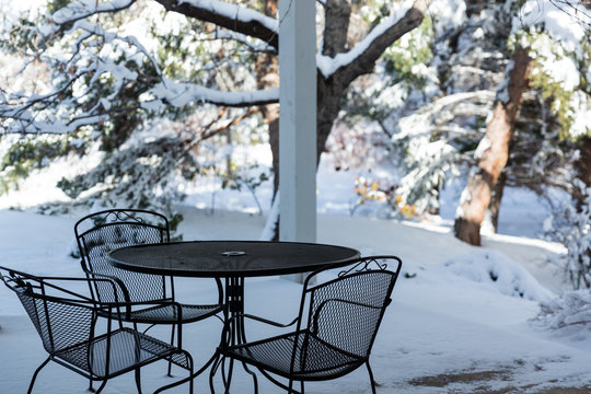 Table and chairs on a snow covered patio in winter