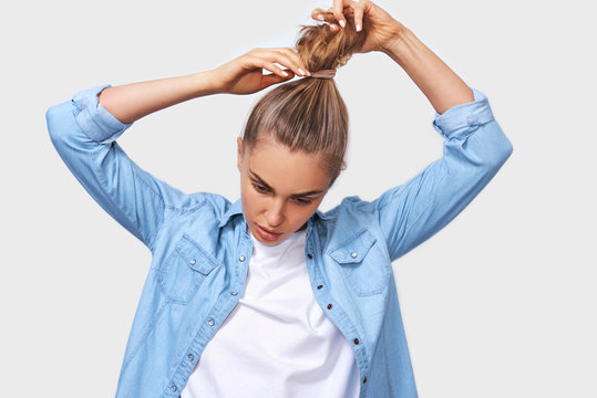 Indoor portrait of young woman collecting hair in a ponytail, wearing blue denim shirt and white t-shirt, posing over white wall. Adorable blonde female makes ponytail, advertises healthy natural hair