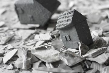 災害で壊れた家屋と瓦礫を見つめる人々