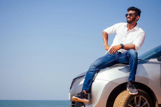 Successful young businessman sunglasses on a beach. Afro man leaning on his car parked in front of ocean on road trip enjoying peace and silence relaxing on nature.Summer vacations and travel concept
